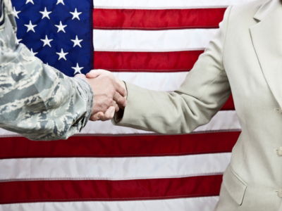 A veteran shaking hands in front of the US flag